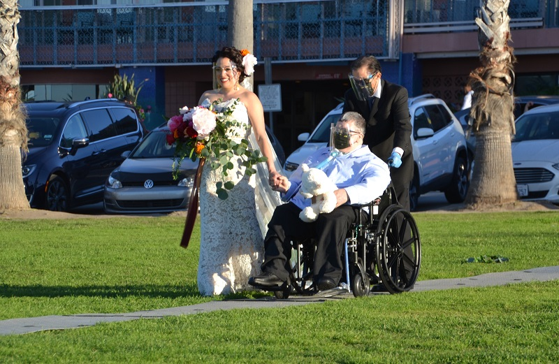 A bride holds her father's hand as they walk down the grey Access Trax pathway over grass at a park. The father is holding a white teddy bear and is seated in his manual wheelchair. Another man assists by pushing the father in his wheelchair. They are all wearing clear face shields due to covid-19 precautions.