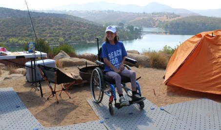 A young woman smiles, seated in her manual wheelchair at her campsite which overlooks a lake. There is an orange tent on the right and a campfire pit behind her. Her wheelchair is on a grey Access Trax accessible pathway.