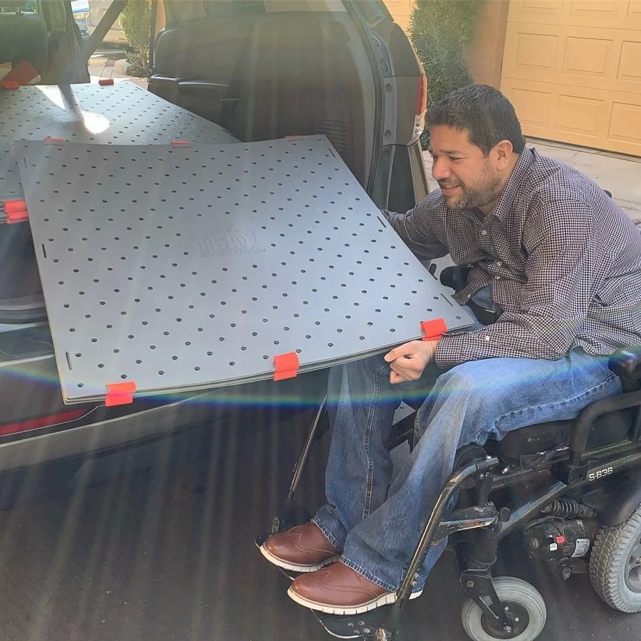 A man in a long sleeve shirt and jeans puts a stack of Access Trax mats in the trunk of his accessible van. He is seated in his power wheelchair and is smiling.