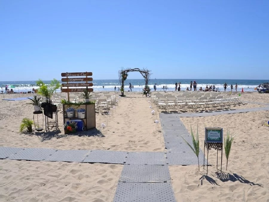 Image shows a beach wedding set up on the sand with an altar, white folding chairs, and signs on a sunny day. There is a grey Access Trax portable pathway over the sand to make the wedding accessible for guests.