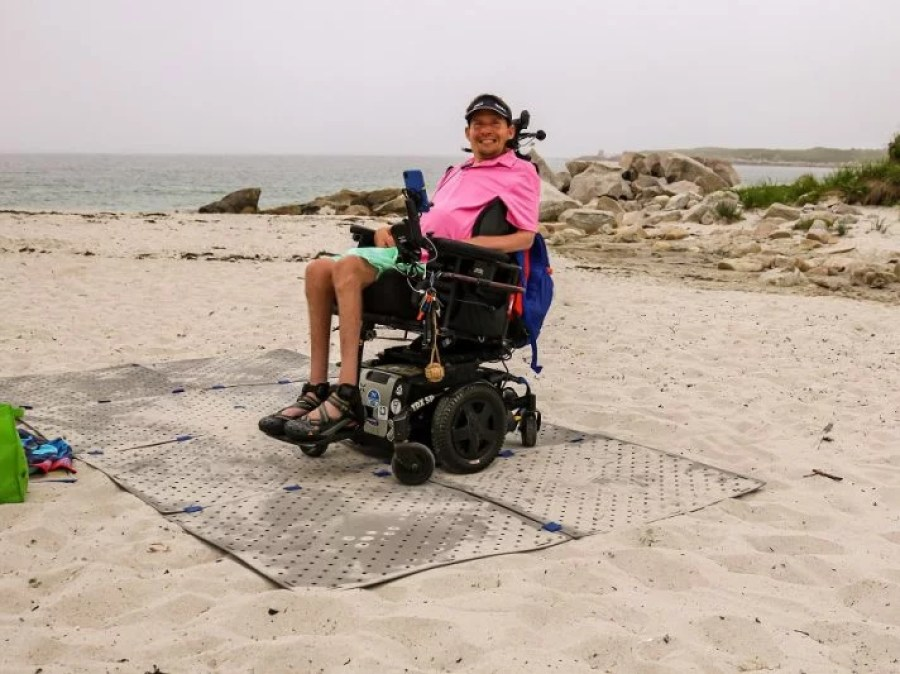 A man wearing a pink collared shirt and green shorts smiles as he sits in his power wheelchair at the beach on top of an Access Trax portable pathway.