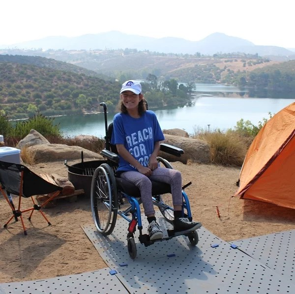 A young woman with brunette hair smiles seated in her manual wheelchair at her campsite which overlooks a lake. Her chair is on a grey Access Trax portable pathway. There is an orange tent on the right.