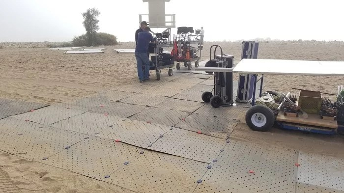 Image shows a grey portable access platform over sand at the beach on a cloudy day. There is film industry equipment on the platform and two men standing near a dolly. There is a small lifeguard tower in the background.