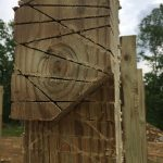 Cutting notches in a post to build a pole frame for a cordwood home