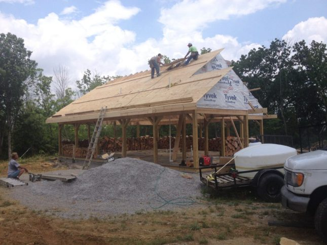 Roofers laying the plywood decking for a metal roof