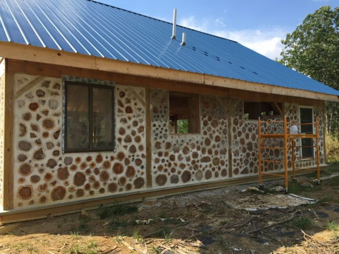 Exterior cordwood wall in progress - at Accidental Hippies