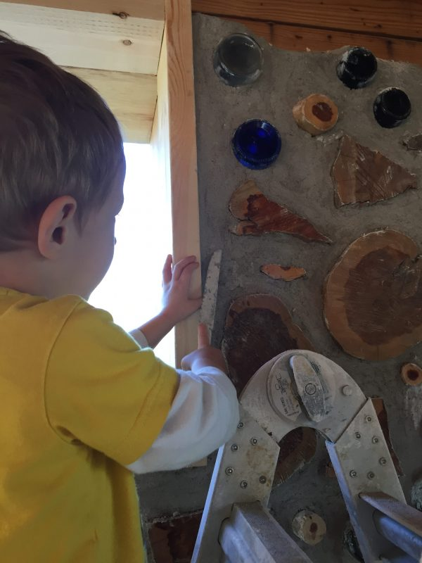 Even our 3-year-old son can help with the cordwood! Here he is smoothing the wall after the adults spent the day building.