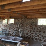 A cordwood wall made with a mix of red cedar logs and white pine posts