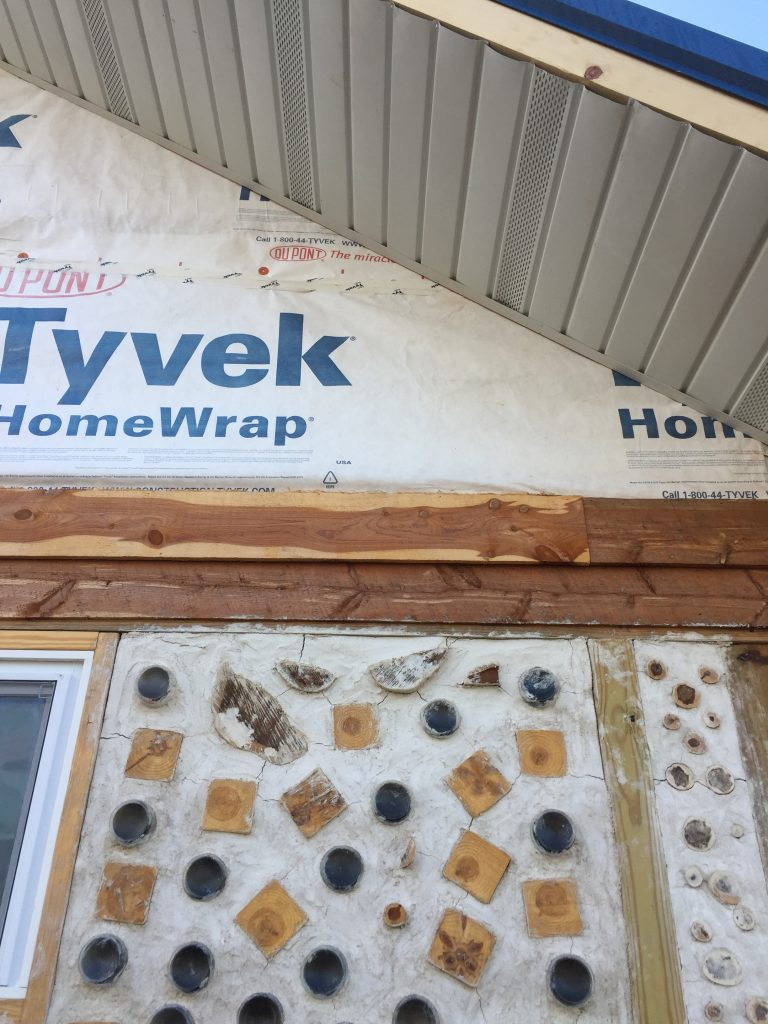 Soffit and cedar siding in progress on the gable end of our cordwood house