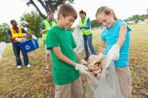 Children clearing up rubbish outdoors. A boy and a girl wearing plastic gloves, holding a bin bag