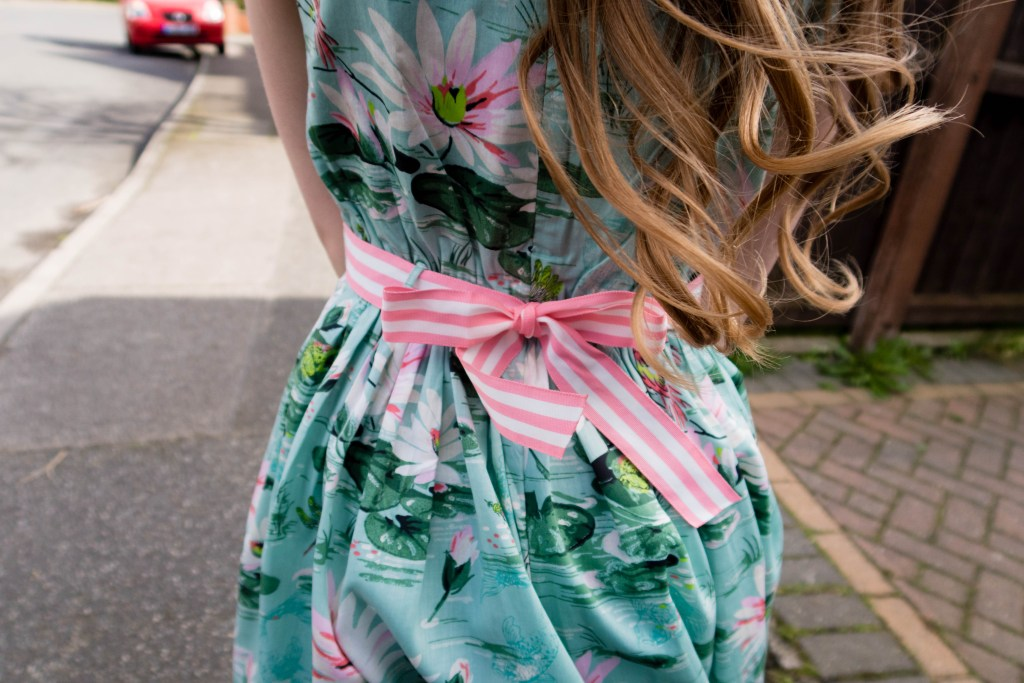 Emma wearing a Monsoons girls spring dresses in a blue/green lily printed paterm with a pink and whie candy striped fabric belt. The belt is tied in a beautiful bow