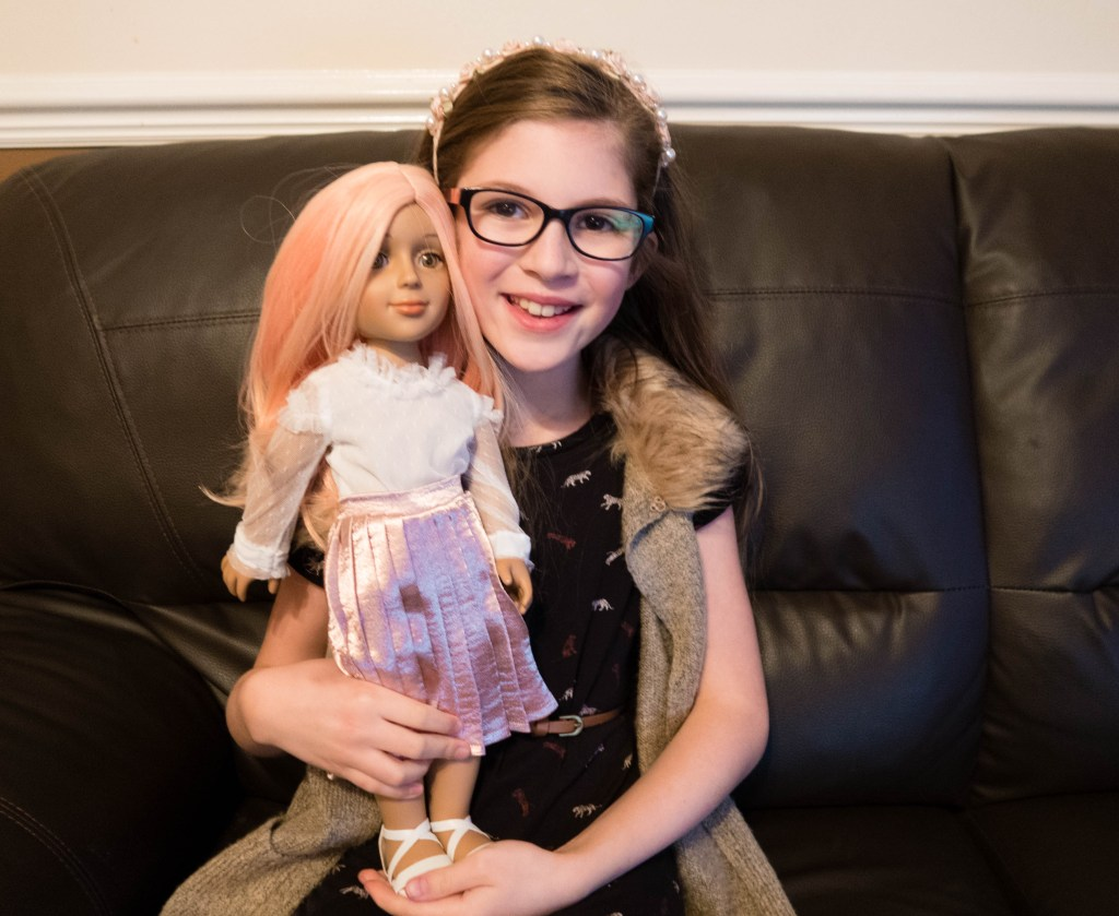 I'M A GIRLY Emma holding the doll in a pink wig