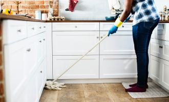 Person mopping Kitchen Floor/Areas to Notice When Cleaning Your New Home