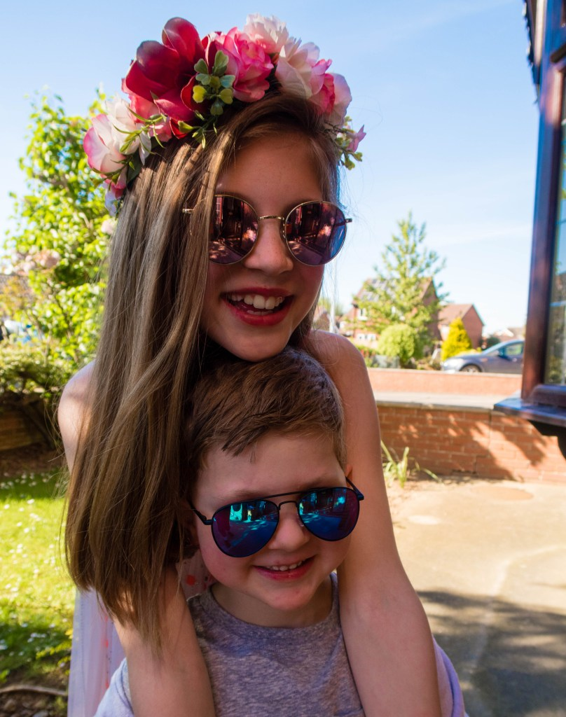 both my kids msiling in sunglasses and hugging