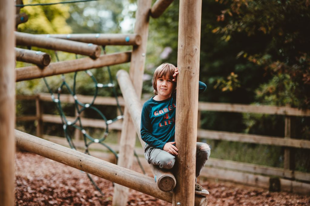 child on large wooden netted climbing frame