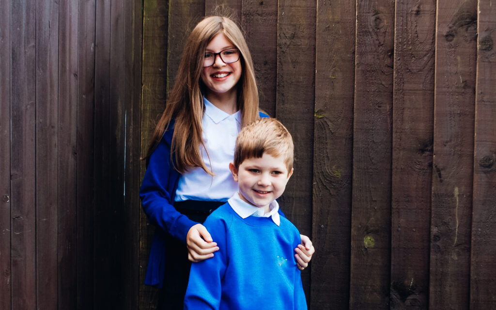 Greg and Emma on the first day of school wearing blue jumpers and standing in front of a fence