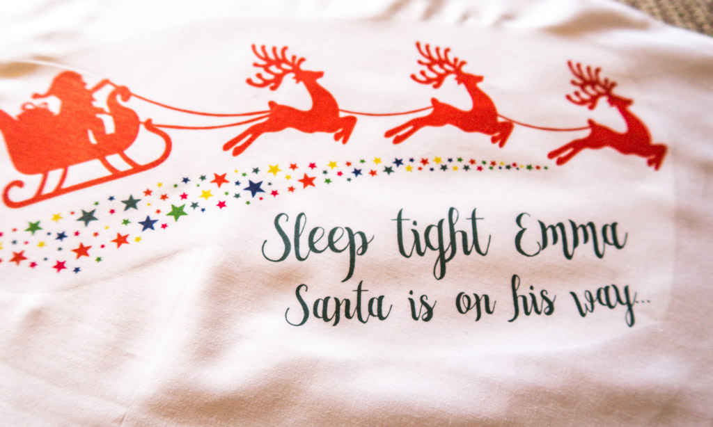 "pillowcase has Santa on a sleigh being pulled by reindeer, text reads ""Sleep tight Emma Santa is on his way"""