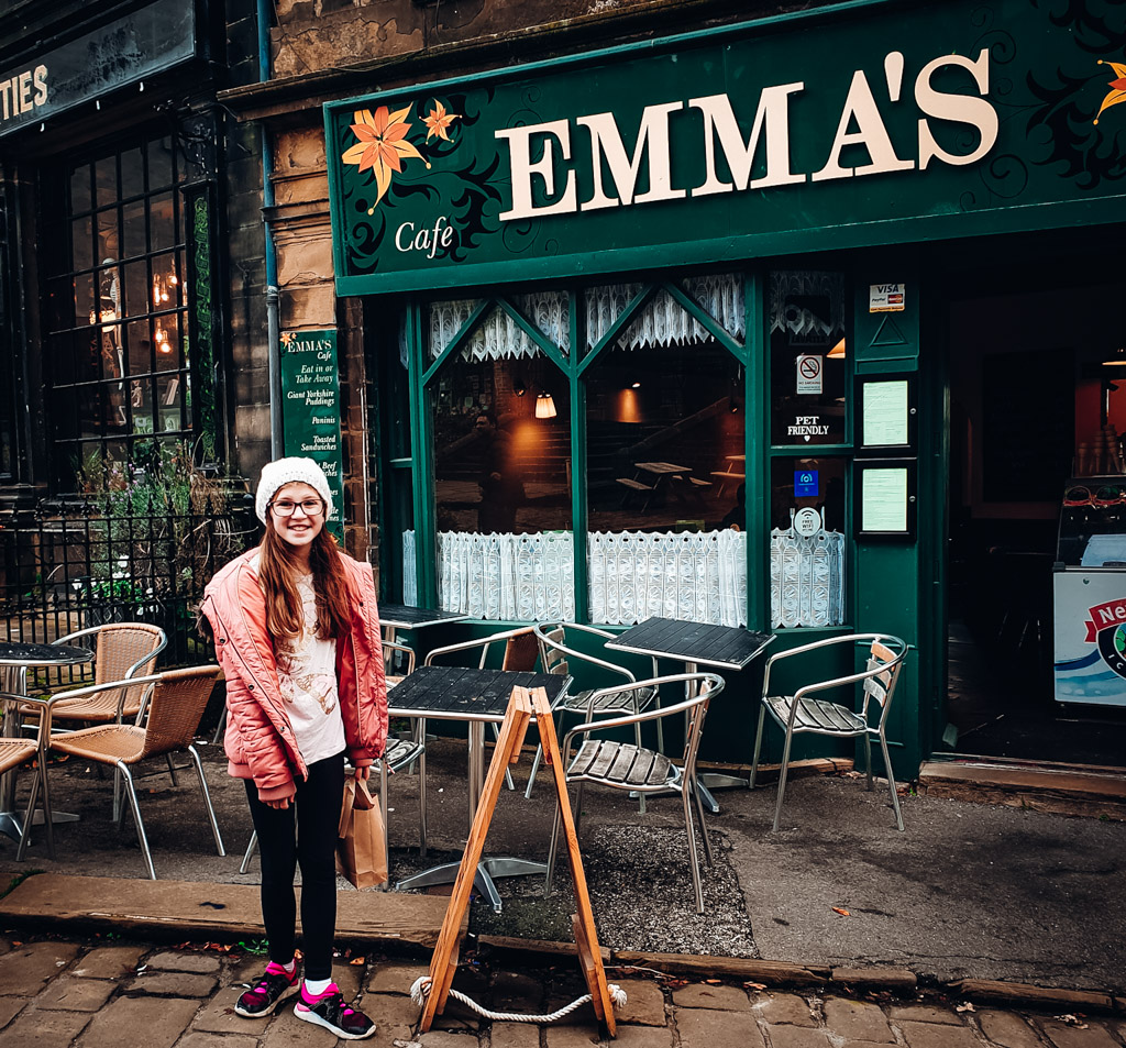My daughter Emma, standing in front of Emma's cafe