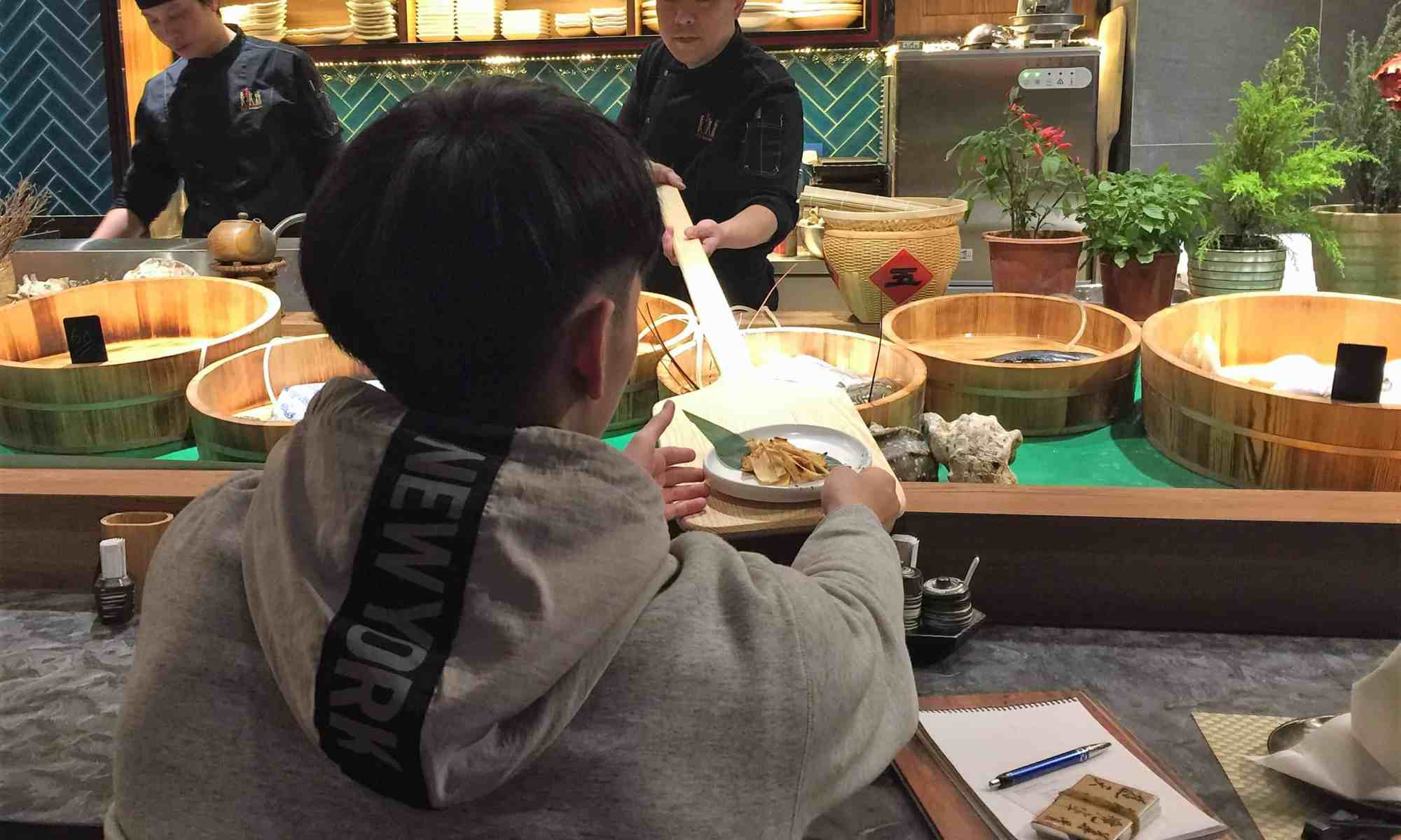 image-of-a-diner-receiving-dish-on-wooden-paddle-at-japanese-restaurant
