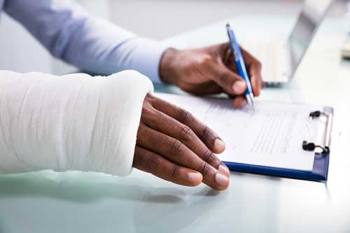 An injured man signing a document