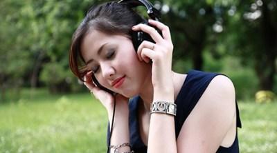 Woman listening through headphones.