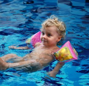 Little girl in inflatable oversleeves floats in swimming pool