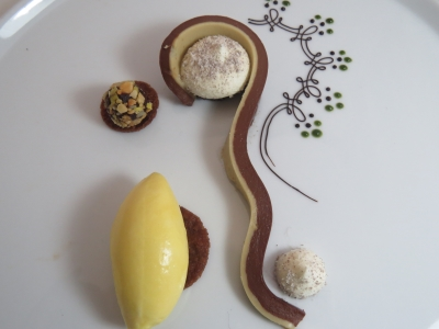 Chocolate textures with tropical fruit accents, dark chocolate and coffee ganache, white chocolate vanilla mousse, chocolate powder, sea salt brownie, chocolate streusel, milk chocolate air cremeux, ginger syrup macarated Brunoise banana and lilikoi sherbet