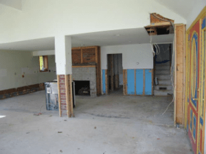 photo of cottage living room and fireplace with walls torn closed after water damage, prior to being remodeled by Acheson Builders