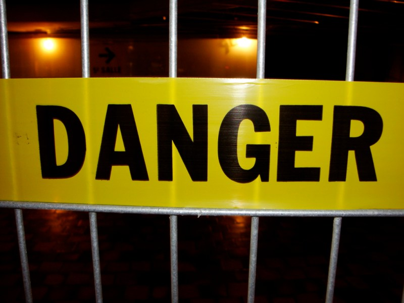 """Yellow tape reading """"Danger"""" outside a construction site"""