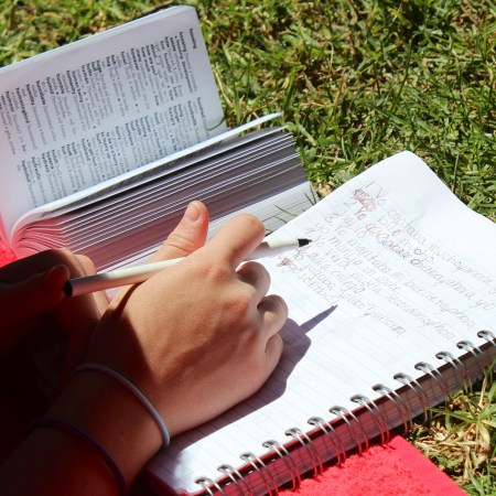 Student consulting dictionary and writing on notebook