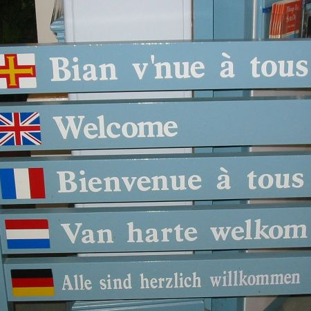 Multilingual welcome sign (Guernésiais on top) at Guernsey tourist information