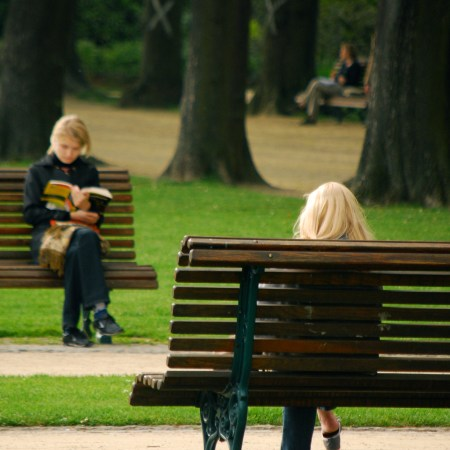Two women, sitting on park benches, reading