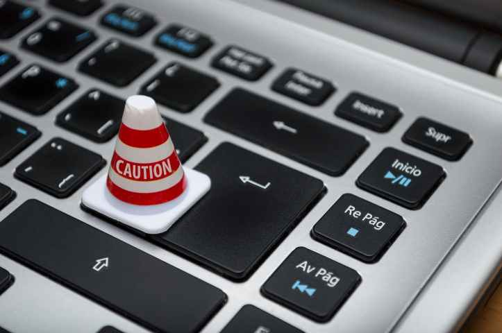 Small plastic cone with the word 'caution', placed on a partially visible laptop keyboard.