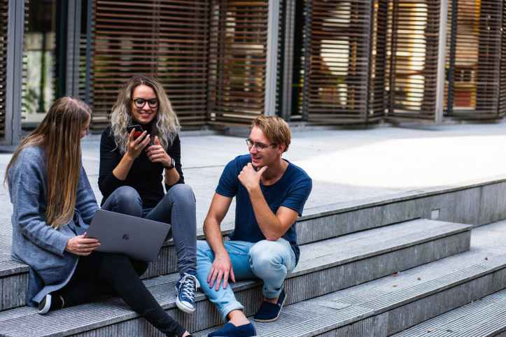 Three university students chatting outdoors