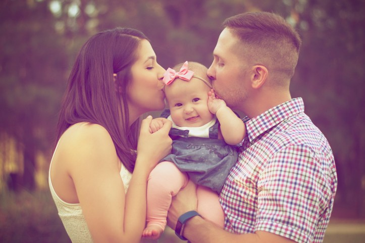 Young couple kissing a baby.
