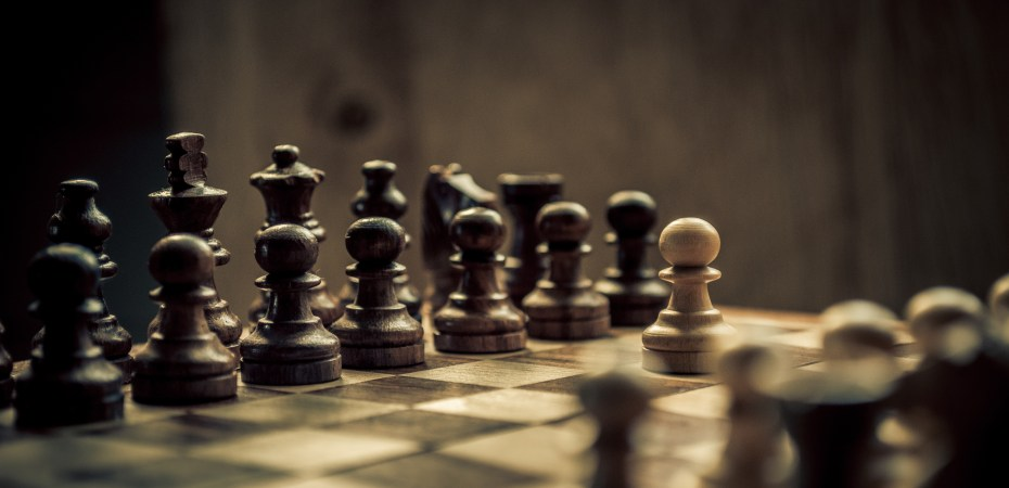 Chess set; one white pawn standing off against a set of black pieces
