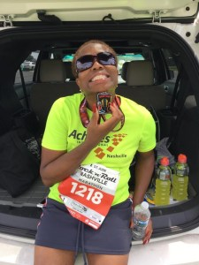 Theresa holding medal and water after Rock and Roll Marathon