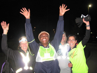 In order from left to right: Guide Amy Harris (in a black jacket ,headlamp, and reflective vest), Athlete Theresa Khayyam (in a blue jacket, headband, and reflective vest, JoAnne Sacks (in a grey shirt, headlamp, and reflective, vest), and Jana Bergman ( in a lime green Achilles shirt and hold gloves) all hands are in the air
