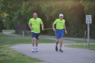 Athlete Ricky Jones on left wearing an Achilles shirt and blue shorts and Guide Peter Pressman on right wearing an Achilles shirt, blue shorts, and white hat