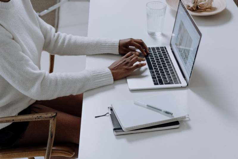 Woman typing on computer with notebook next to her