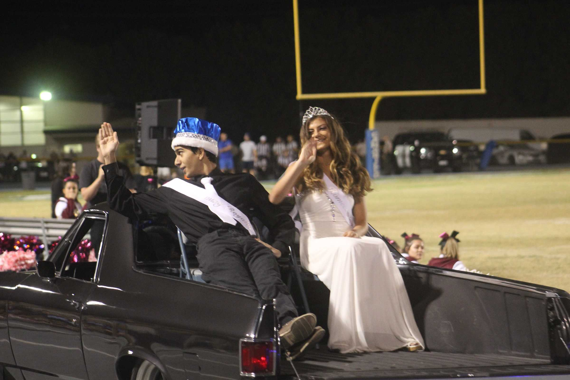 Ramtein Foghi and Sophia Cortina, junior homecoming royalty, waving to the crowd as they drive down the Cam High track during the Homecoming Game Halftime Show.