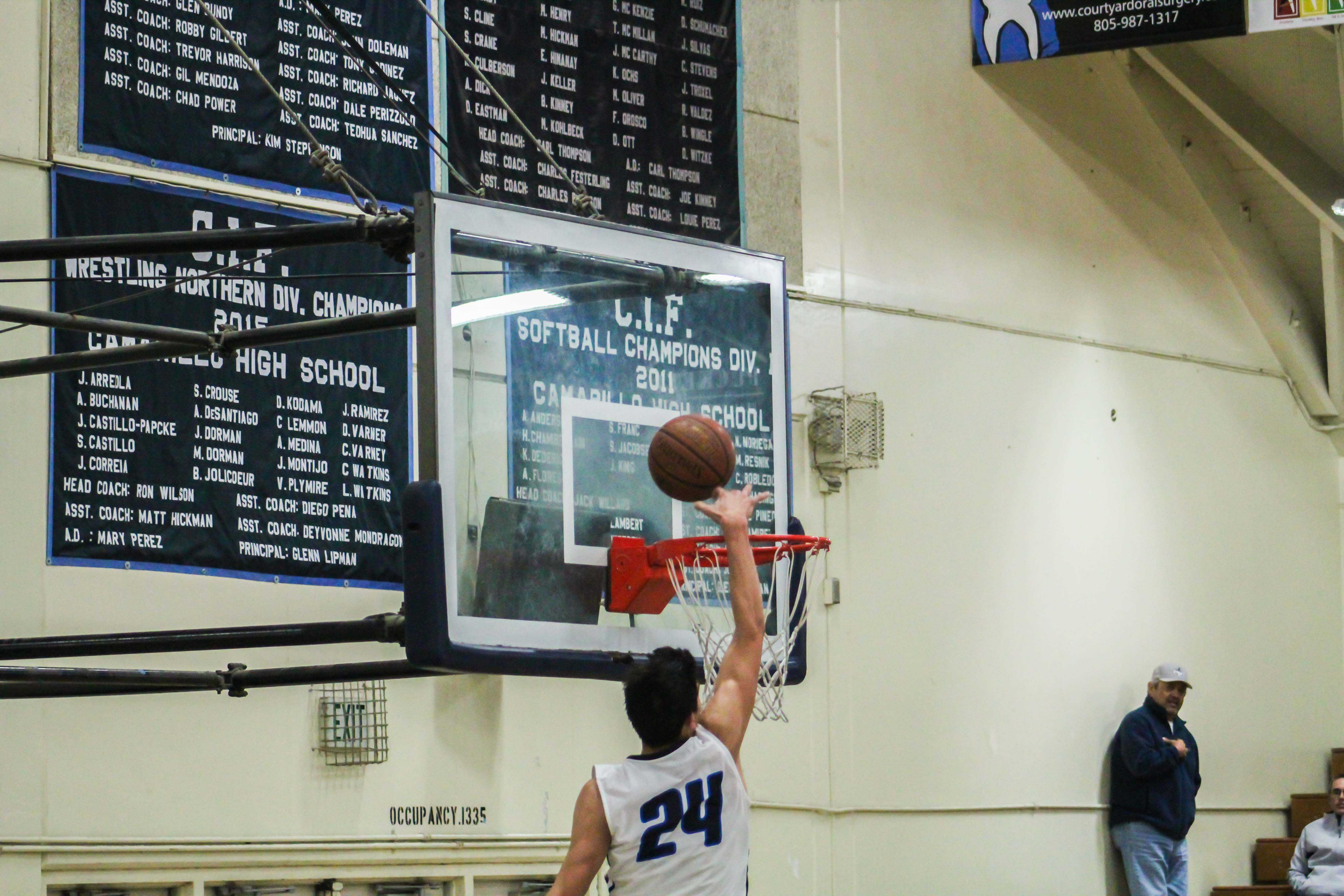 Jaime Jaquez, sophomore, attempts a dunk with an impressed on-looker.