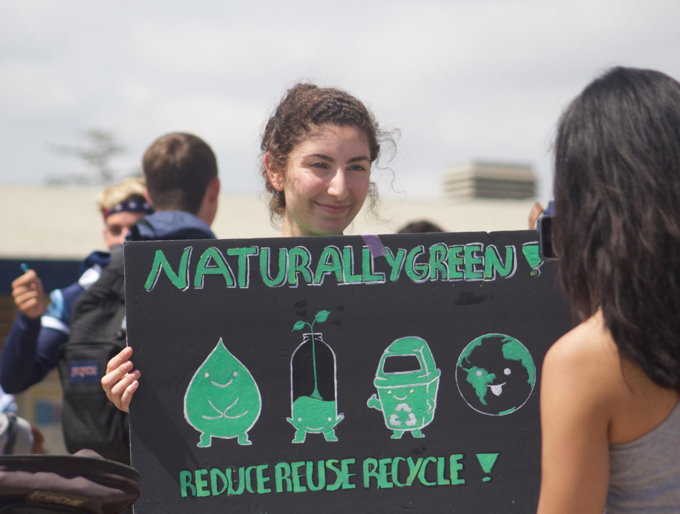 Naturally Green's Tamar Nachian, senior, shows off a handmade poster to promote the eco-friendly club.