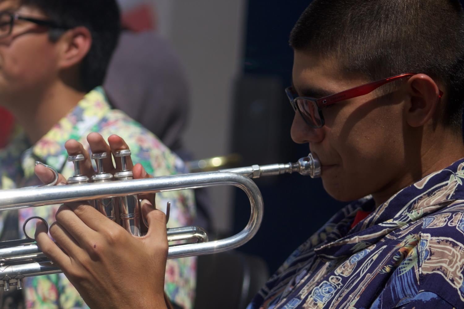 Jazz Club President Mauricio Castellanos, junior, plays a few notes at club rush.