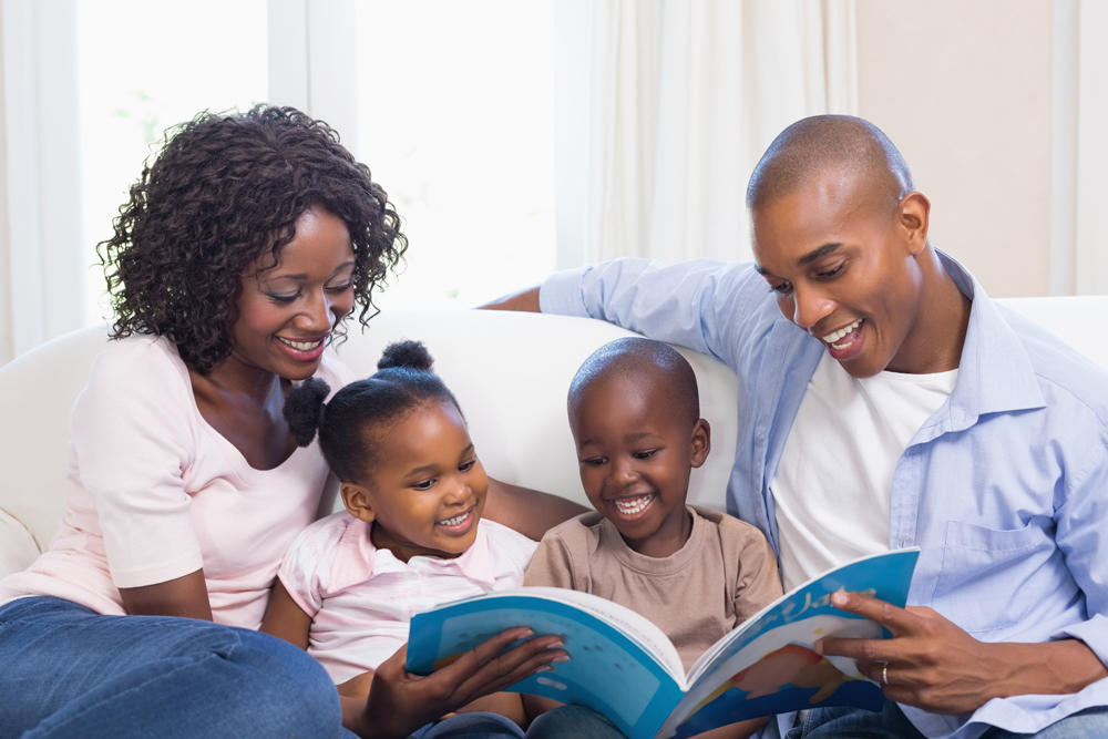 Happy family on the couch reading storybook at home in the living room