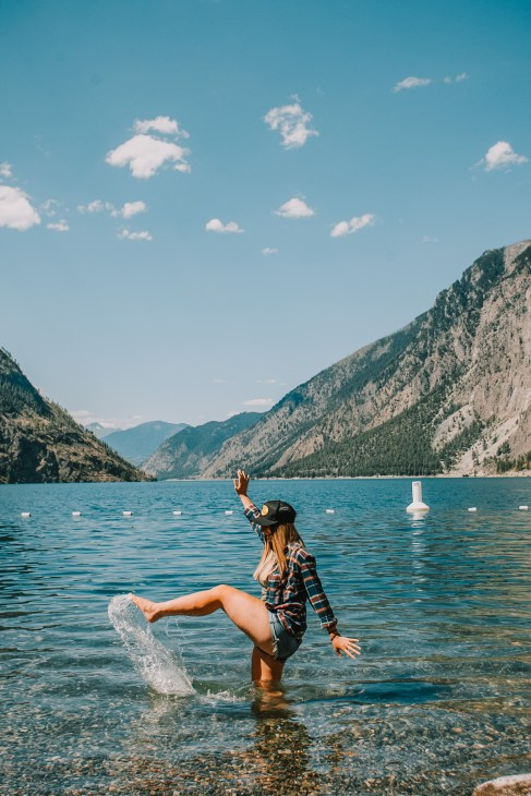 Photo of a girl kicking up water in a clear blue lake with a mountain drop in the background.