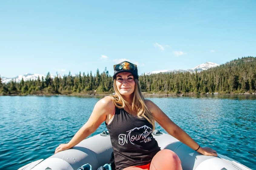 Boating on Cirque Lake.  Photo of a woman wearing a black tank top and black cap sitting in an inflatable boat smiling at the camera. In the background is a blue lake with green trees and moutian tops and blue skies.