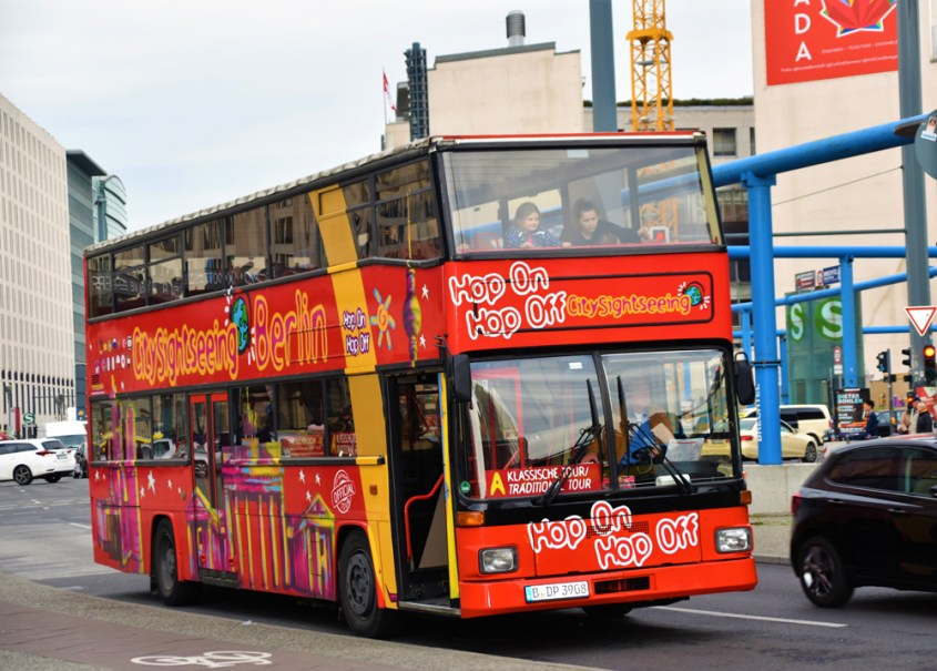 A double decker red bus driving through a city with passengers on board.