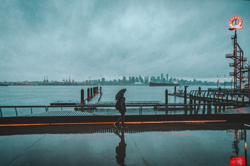 A person walking in the rain with an umbrella along a pier with the river behind and a cityscape on the other side.