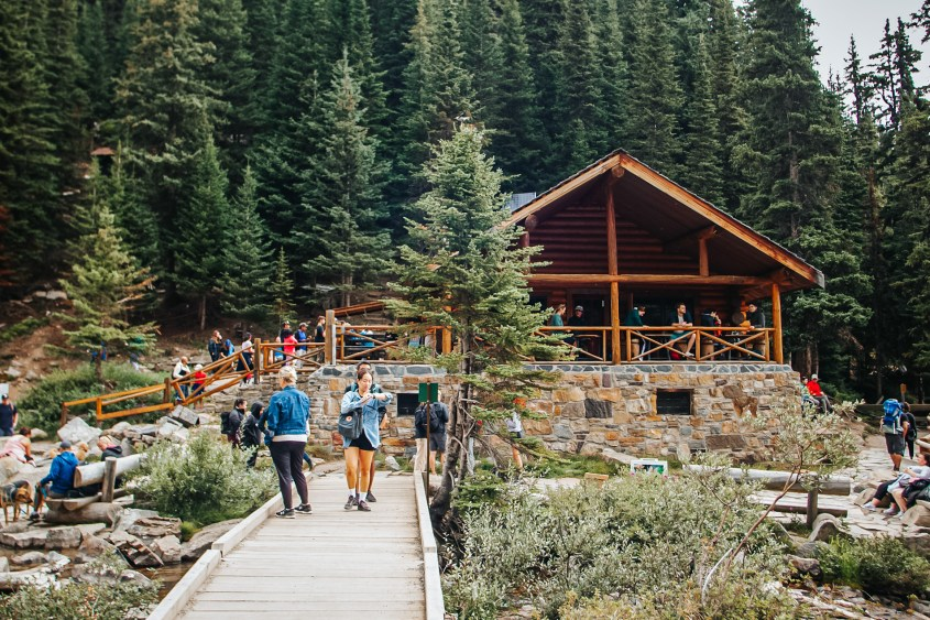 Photo of a forest scene with a log cabin and crowds of people around it.  Lake Agnes Tea House in Lake Louise, Canada
